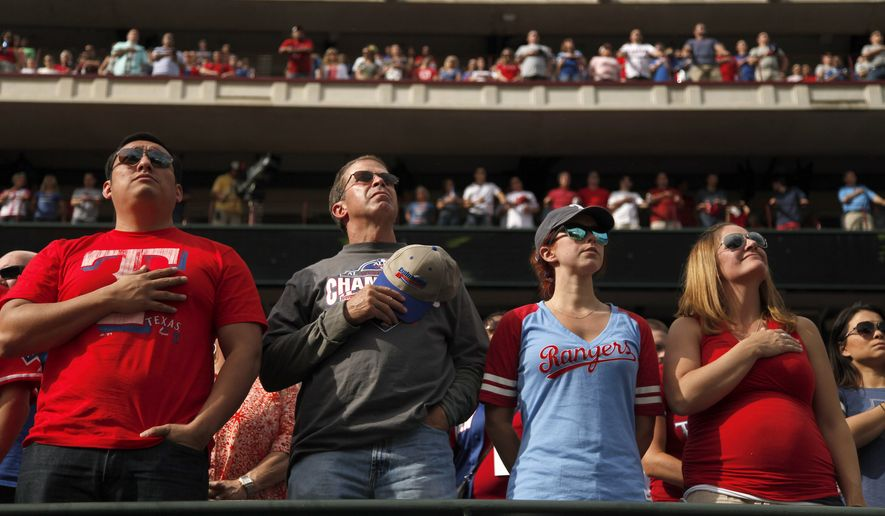 "Texas Rangers fans stand for ""God Bless America"" during the seventh-inning stretch during the team's home opener against the Houston Astros in Arlington, Texas, on April 10, 2015. (Associated Press)"