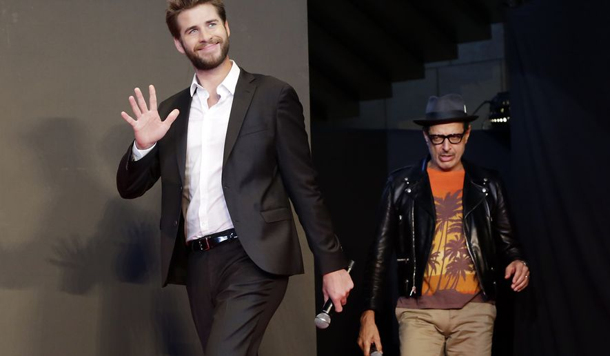 """Actors Liam Hemsworth, left, and Jeff Goldblum walk in the stage during a promotional event for the movie """"Independence Day: Resurgence"""" in Tokyo, Thursday, June 30, 2016. Mr. Hemsworth was named by PETA on July 7 as the sexiest male vegetarian celebrity of 2016 (AP Photo/Eugene Hoshiko)"""