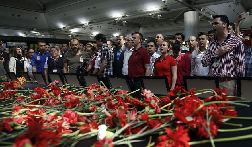 Family members, colleagues and friends of the victims of Tuesday blasts gather for a memorial ceremony at the Ataturk Airport in Istanbul, Thursday, June 30, 2016.  A senior Turkish official on Thursday identified the nationalities of Istanbul airport attackers after police carried out raids looking for Islamic State suspects. (AP Photo/Emrah Gurel)