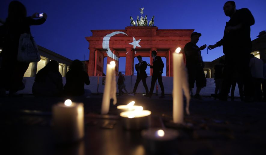 Candles are placed in front the Brandenburg Gate in Berlin, Wednesday, June 29, 2016. The Brandenburg Gate was illuminated with Turkey's national flag after suicide attackers killed dozens and wounded more than 140 at Istanbul's busy Ataturk Airport late Tuesday, the latest in a series of bombings to strike Turkey in recent months. (AP Photo/Markus Schreiber)