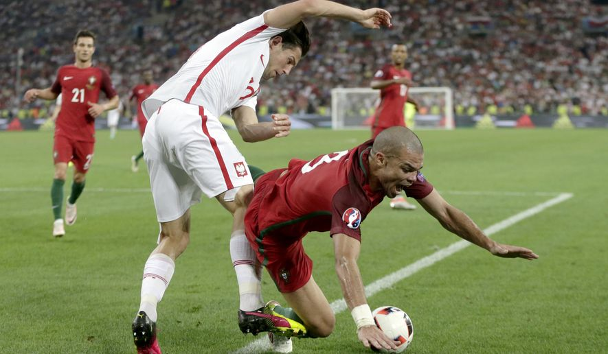 Portugal's Pepe, right, falls after a tackle by Poland's Grzegorz Krychowiak during the Euro 2016 quarterfinal soccer match between Poland and Portugal, at the Velodrome stadium in Marseille, France, Thursday, June 30, 2016. (AP Photo/Petr David Josek)