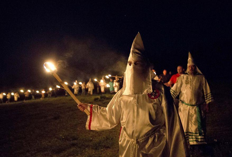 "In this Saturday, April 23, 2016, photo, members of the Ku Klux Klan participate in cross burnings after a ""white pride"" rally in rural Paulding County near Cedar Town, Ga. (AP Photo/John Bazemore) ** FILE **"