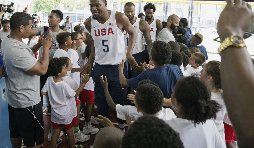 The U.S. men's Olympic basketball team player Kevin Durant greets kids who participated in a basketball clinic as he arrives for a news conference Monday, June 27, 2016, in New York. (AP Photo/Mary Altaffer)