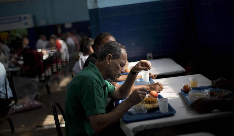 People have lunch at the Central do Brasil soup kitchen, in Rio de Janeiro, Brazil, Thursday, June 30, 2016. Some of Rio de Janeiro's busy soup kitchens are shutting down because the cash-strapped state has failed to pay suppliers that serve cheap meals to the poor. It's the latest fallout from a financial crisis that is also fueling worries about security and public transportation during the summer olympic games slated to begin Aug. 5.(AP Photo/Silvia Izquierdo)