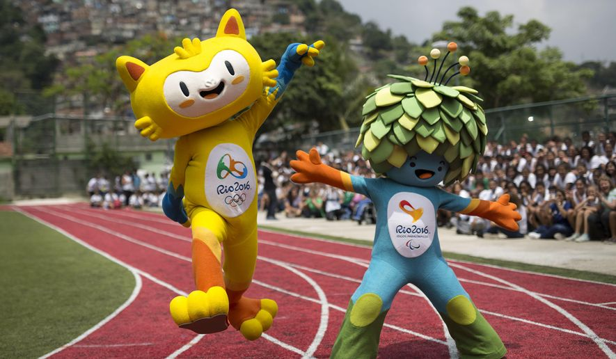 """FILE - In this Nov. 24, 2014, file photo, the mascots of the Rio 2016 Olympics, left, and Paralympic Games make their first official appearance at a public school in the Santa Teresa neighborhood of Rio de Janeiro, Brazil. The Rio de Janeiro Olympics suddenly became a tangible reality. One of its so-called """"Mega"""" souvenir shops opens Friday July 1, on Copacabana Beach. (AP Photo/Felipe Dana, File)"""