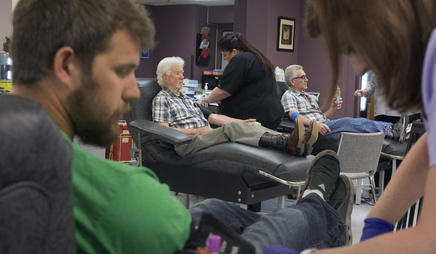 ADVANCE FOR USE SATURDAY JULY 2, 2016 AND THEREAFTER - Three generations of blood donors, Trenton Tedrick, right, Delbert Tedrick, center, and Robin Dedrick, donate blood together at the Rock River Valley Blood Center Monday, June 6, 2016 in Rockford, Ill. Delbert Tedrick has donated 18 gallons, and his son, Robin, hit the five-gallon milestone. Tedrick's 18-gallon lifetime blood donation serves as an example for younger donors in his family, and it's a precedent that the Rock River Valley Blood Center considers invaluable. (Sunny Strader/Rockford Register Star via AP)  MANDATORY CREDIT
