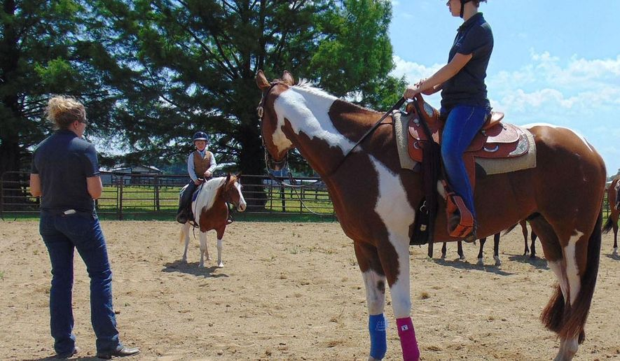 In this June 11, 2016 photo Rachel Higgs, right, sits on Simon, a 8-year-old paint bred horse during a 4-H Horse Clinic at the Effingham County Fairgrounds in Effingham, Ill. Dana Grupe, Effingham County 4-H Horse Superintendent, provided an estimated 25 young people between the ages of 5 and 18 the rules of riding horses, tack, horsemanship and attire. (Dawn Schabbing/Effingham Daily News via AP) MANDATORY CREDIT