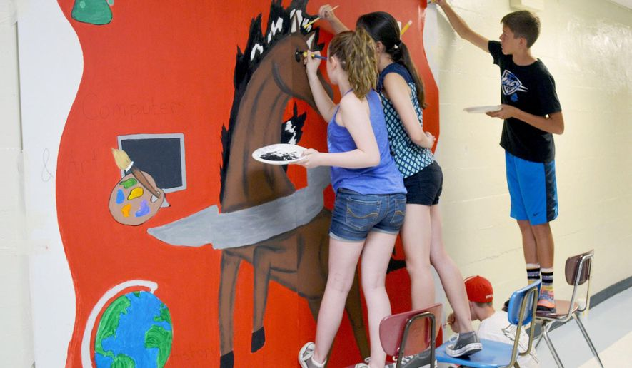 ADVANCE FOR USE SUNDAY, JULY 3, 2016 AND THEREAFTER - In this May 31, 2016 photo, from left, Josie Forbes, Janette Bovard, Aiden Beck, Dylan Ritz, work painting a mural in the cafeteria at Effingham Junior High School in Effingham, Ill. For most students, summer marks a three-month-long detachment from school and from learning. However, the foursome are spending the summer painting the mural to leave their legacy at the school. (Kaitlin Cordes /Effingham Daily News via AP) MANDATORY CREDIT