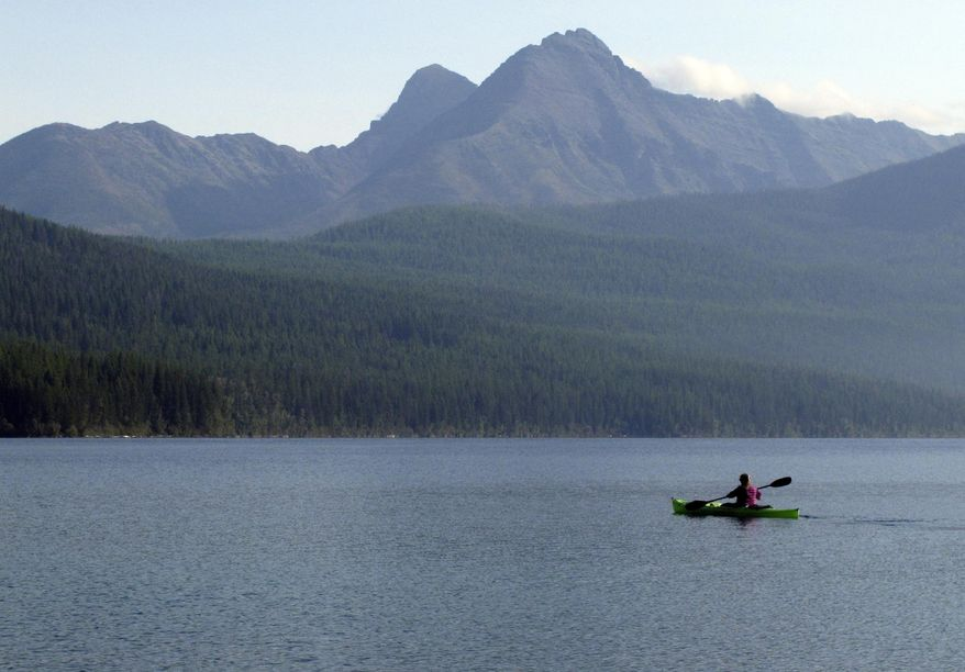 In this Sept. 6, 2013, file photo, a woman kayaks on Kintla Lake in Glacier National Park, Mont. A grizzly bear attacked and killed a 38-year-old mountain biker Wednesday, June 29, 2016, as he was riding along a trail just outside the national park, Montana authorities said. (AP Photo/Matt Volz, File)