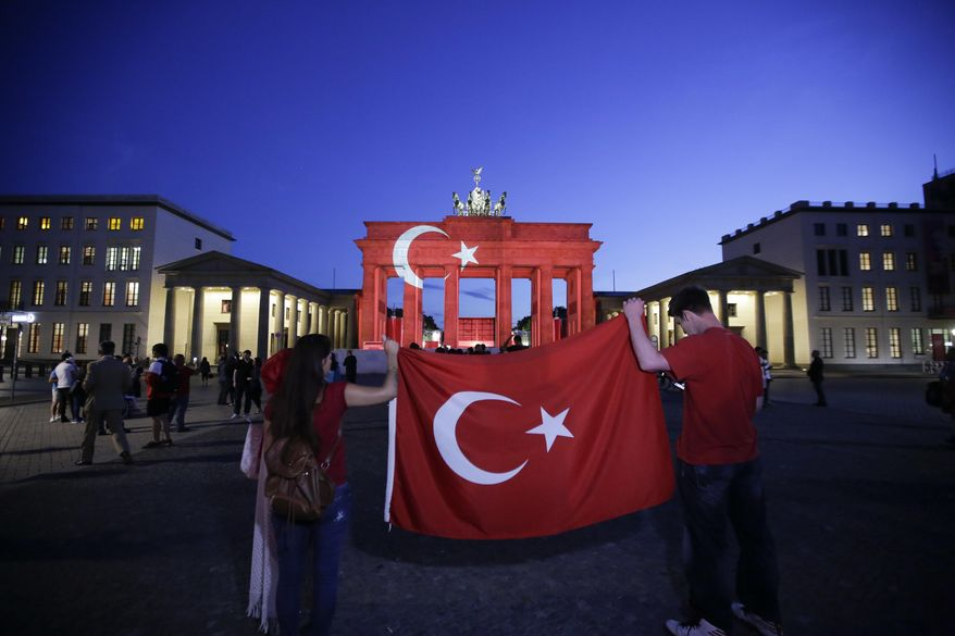 Two people hold a Turkish flag in front of the Brandenburg Gate in Berlin, Wednesday, June 29, 2016. The Brandenburg Gate was illuminated with Turkey's national flag after suicide attackers killed dozens and wounded more than 140 at Istanbul's busy Ataturk Airport late Tuesday, the latest in a series of bombings to strike Turkey in recent months. (AP Photo/Markus Schreiber)