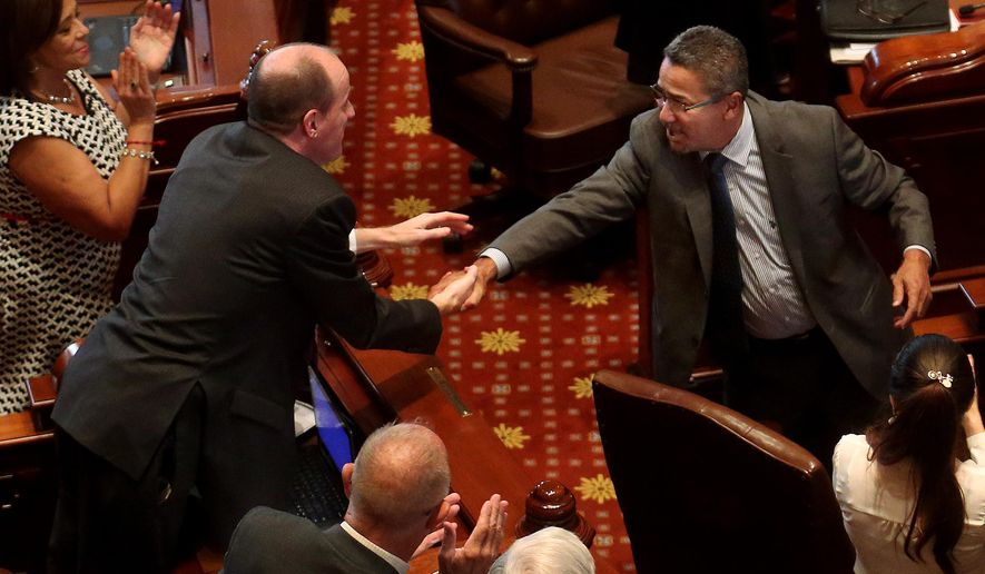 Sen. William Delgado, D-Chicago, right, who is retiring from the Senate this week, shakes hands with fellow senator Bill Cunningham, D-Chicago, during a standing ovation on the Senate floor in Springfield, Ill., Wednesday, June 29, 2016. Wednesday, June 29, 2016. Illinois lawmakers and Republican Gov. Bruce Rauner were trying to craft a short-term budget deal Wednesday to ensure public schools open this fall and other services are funded while a fight over a full spending plan continues. (David Spencer/The State Journal-Register via AP) MANDATORY CREDIT