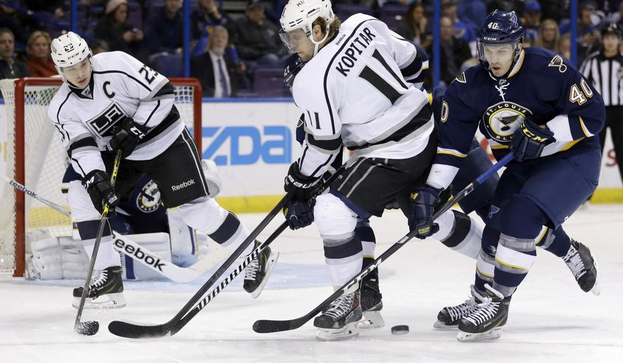 FILE - In this Dec. 16, 2014, file photo, St. Louis Blues' Maxim Lapierre, right, and Los Angeles Kings' Anze Kopitar chase a loose puck as Kings' Dustin Brown, left, watches during an NHL hockey game in St. Louis. Brown doesn't agree with the Kings' decision to strip him of their captaincy after eight seasons and two Stanley Cups. Brown aired his displeasure in a phone interview Thursday, June 30, 2016, two weeks after the Kings appointed Kopitar as their new captain. (AP Photo/Jeff Roberson, File)