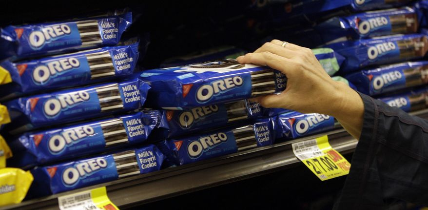 FILE - In this Feb. 9, 2011, file photo, a shopper selects Oreo cookies at a Ralphs Fresh Fare supermarket in Los Angeles. Shares of Hershey are soaring Thursday, June 30, 2016, after a report that it could be taken over by Oreo cookie maker Mondelez International. (AP Photo/File)