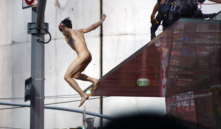 EDS NOTE: NUDITY - A naked man jumps off the rear staircase ledge above the TKTS Broadway ticket booth in New York's Times Square, Thursday, June 30, 2016. Police said the man, who was shouting about presumptive Republican presidential nominee Donald Trump, was conscious after the jump of about 16 feet off the booth.  (AP Photo)
