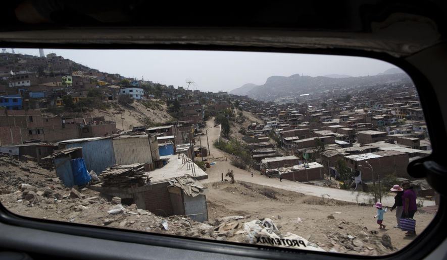 This March 11, 2016 photo, shows the view from a van carrying U.S. tourists on a tour of a shanty town, in the Villa Maria del Triunfo district on the outskirts of Lima, Peru. While most tourists come to Peru to see the Incan citadel of Machu Picchu or sample its renowned cuisine, some also visit the impoverished shantytowns in its massive capital. (AP Photo/Rodrigo Abd)