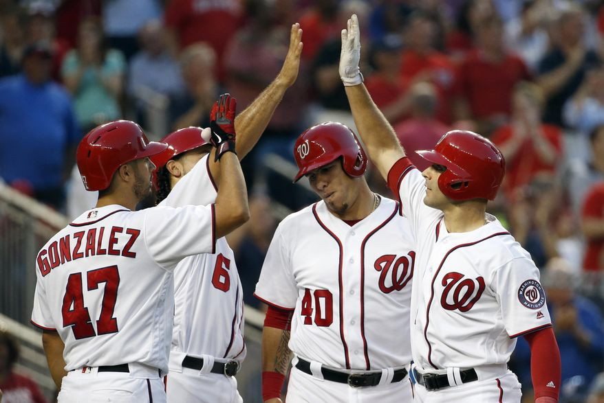Washington Nationals' Danny Espinosa, right, celebrates his grand slam with Gio Gonzalez (47), Anthony Rendon (6) and Wilson Ramos (40) during the third inning of a baseball game against the Cincinnati Reds, Thursday, June 30, 2016, in Washington. (AP Photo/Alex Brandon)
