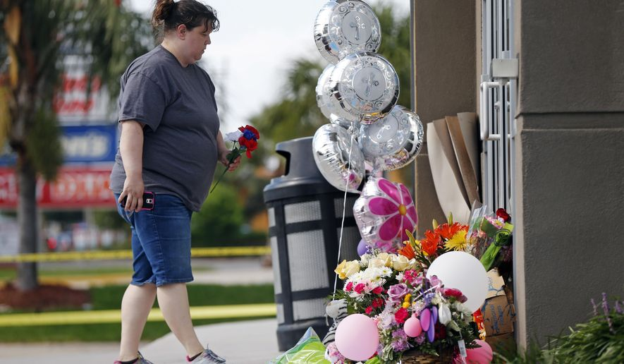 Penny Sevin, of Picayune, Miss., places a flower at a makeshift memorial outside the Raising Cane's franchise in Kenner, La., Thursday, June 30, 2016. Kenner police have arrested a second man, are questioning a third and are looking for a woman in the stabbing death of restaurant manager Taylor Friloux, 21, during an armed robbery. (AP Photo/Gerald Herbert)