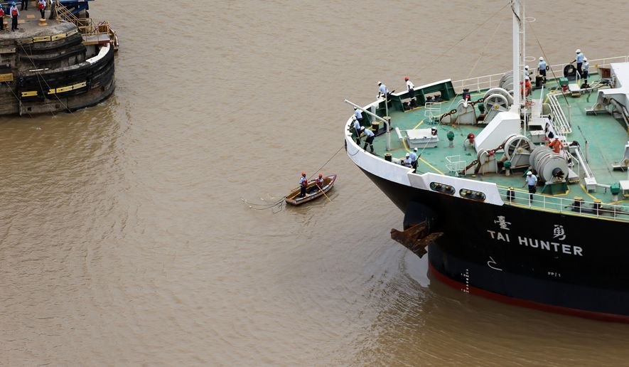 In this June 25, 2016 photo, two canal workers on a small rowboat catch a line from a massive cargo ship as it prepares to enter the Pedro Miguel locks in Panama City. As a major Latin American hub of finance, commerce and transportation, the Panamanian capital is a growing destination for business travelers. For anyone looking to duck out of a convention center for a few hours, fill a gap between meetings or even if you've just got a long layover at the airport, a visit to Panama City's No. 1 attraction and its newly expanded locks makes for the perfect side excursion. Although the Pedro Miguel locks do not have a visitor's center, the parking lot offers a good viewpoint to see the activity at the locks. (AP Photo/Dario Lopez-Mills)