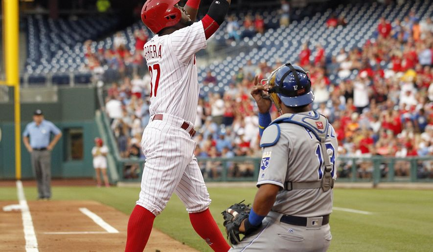 Philadelphia Phillies' Odubel Herrera, left, points skyward as he walks past Kansas City Royals catcher Salvador Perez after hitting a solo home run during the first inning of a baseball game Friday, July 1, 2016, in Philadelphia. (AP Photo/Tom Mihalek)