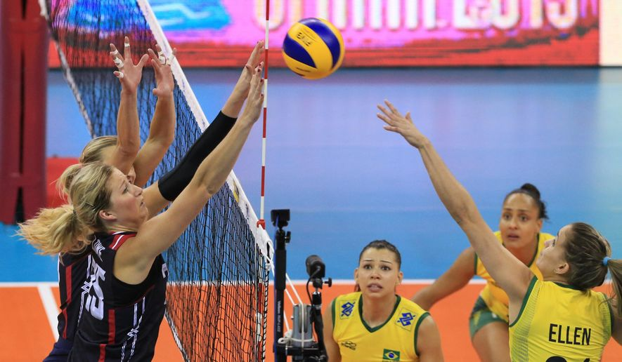 FILE- In this July 25, 2015, file photo, Brazil's Ellen Braga (21) spikes the ball against a block by United States' Karsta Lowe (25) and Christa Harmotto Dietzen, left rear, in an FIVB World Grand Prix Finals volleyball match in Omaha, Neb. The close-knit U.S. squad believes it has built the right mix to challenge for the top spot on the podium this August in Rio de Janeiro. The Americans have developed a culture they are counting on being the right one. (AP Photo/Nati Harnik)