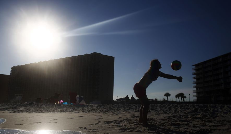 """In this, Friday, July 1, 2016, Bevin Walker, 12, of Sylacauga, Ala., plays volleyball near the shoreline with her family in Orange Beach, Ala. A long, busy holiday weekend along the Gulf Coast and elsewhere is helping boost a surge in tourism in Alabama, and officials hope visitors will set another record for spending in 2016. Industry leaders say hotels and condominiums in Baldwin County are reporting high occupancy rates for the July 4 holiday, which coastal tourism promoter Kay Maghan said is considered the """"super peak""""of the beach season. (AP Photo/Brynn Anderson)"""
