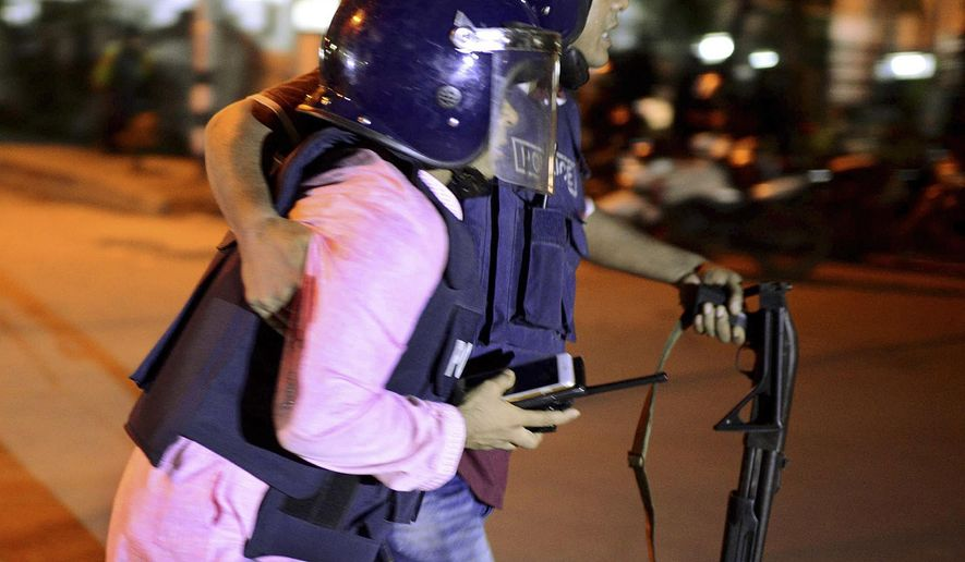 An unidentified security personnel is taken for medical attention after a group of gunmen attacked a restaurant popular with foreigners in a diplomatic zone of the Bangladeshi capital Dhaka, Bangladesh, Friday, July 1, 2016. A group of gunmen attacked a restaurant popular with foreigners in a diplomatic zone of the Bangladeshi capital on Friday night, taking hostages and exchanging gunfire with security forces, according to a restaurant staff member and local media reports. (AP Photo)