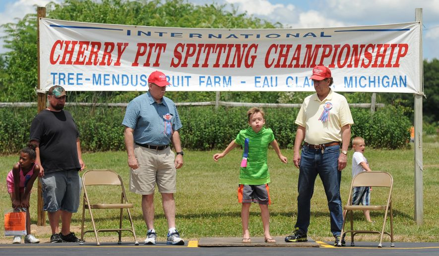 Reid Gillis, from Granger, Ind., is flanked by Berrien County Judge Sterling Schrock, left, and Berrien County Judge John Donahue during the 43rd International Cherry Pit-Spitting Championship Saturday, July 2, 2016, at Tree-Mendus Fruit Farm in Eau Claire, Mich.  (Don Campbell/The Herald-Palladium via AP)