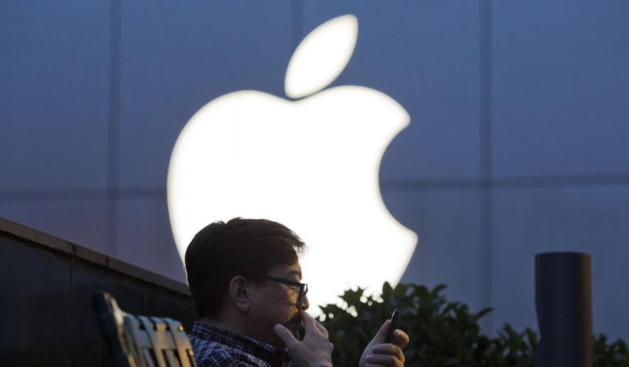 FILE - In this Friday, May 13, 2016 file photo, a man uses his mobile phone near an Apple store logo in Beijing, China. A Beijing court said in an online statement Thursday, June 30, 2016, that Apple is being sued by a subsidiary of China's broadcasting regulator over a propaganda film more than 20 years old, in the latest legal wrangling for the tech giant in China in recent weeks. (AP Photo/Ng Han Guan)