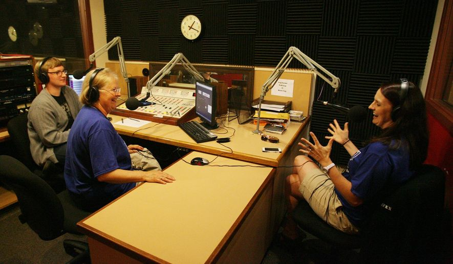 ADVANCE FOR USE SATURDAY, JULY 2 - In this photo taken June 25, 2016, Sharon Behl Brooks, center, associate professor of Journalism/Media Arts and English, speaks with Hastings College senior Sam Bennett and 2006 alumnus Meghan May on the air in the KFKX studio at the Gray Center for Communication Arts in Hastings, Neb.,  during a reunion and send off for the radio station. Amy Roh/The Hastings Tribune via AP)