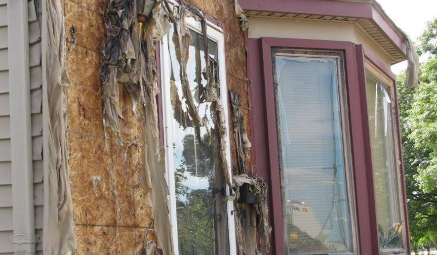 Intense heat from a fire melted the siding on homes on South Dearborn Street in Melvindale, Mich., Saturday, July, 2, 2016. A 24-year-old man took a wrong turn, crashed through a fence and ruptured a natural gas line in suburban Detroit, causing a dramatic explosion in the wee hours Saturday that forced the evacuation of nearby residents and even melted siding off a house, police said. (AP Photo/Ed White)