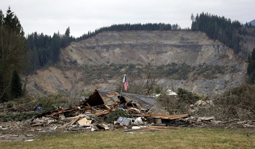 FILE--In this March 25, 2014, file photo, a flag stands in the ruins of a home left at the end of a deadly mudslide from the now-barren hillside seen about a mile behind in Oso, Wash. Washington state and the Stillaguamish Tribe are arguing over whether the tribe might face liability for the devastating landslide of 2014. (AP Photo/Elaine Thompson, File)