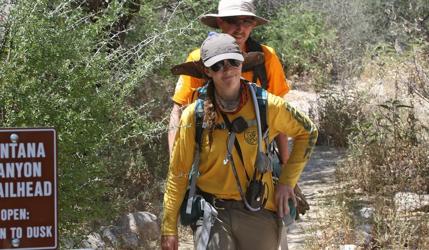 FILE - In this June 20, 2016, file photo, Kara O'Brien and Jeff Mayhew, with the Southern Arizona Rescue Association, return from walking along the Ventana Canyon Trail after searching for a lost hiker in the Santa Catalina Mountains outside Tucson, Ariz. When the temperature spikes, Phoenix trails will stay open for man but not for man's best friend. City leaders on Thursday, June 30, 2016, rejected a proposal to prohibit people from hiking in extreme heat, but they approved a rule banning dogs from the city's 41 trailheads when the mercury climbs to 100 degrees. (A.E. Araiza/Arizona Daily Star via AP)
