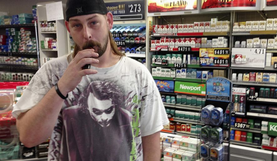 In this June 23, 2016 photo, Kenneth Houser takes a puff on an electronic cigarette at the We B Smokin store where he works in Jefferson City, Mo. Houser says he has smoked traditional cigarettes since age 13 but is trying to quit, partly because of the potential for prices to rise under a pair of tobacco tax initiatives proposed for the Missouri ballot. (AP Photo/David A. Lieb)