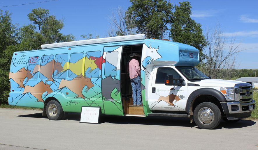 In this June 15, 2016, photo, a bus that has been retrofitted with an art studio and space for a bank teller is seen in the parking lot of a college in Pine Ridge, S.D., to allow people to take a free featherwork classes. The bus is crisscrossing South Dakota's Pine Ridge Indian Reservation to provide emerging artists a space to take and teach arts classes and learn more about the arts business. (AP Photo/Regina Garcia Cano)