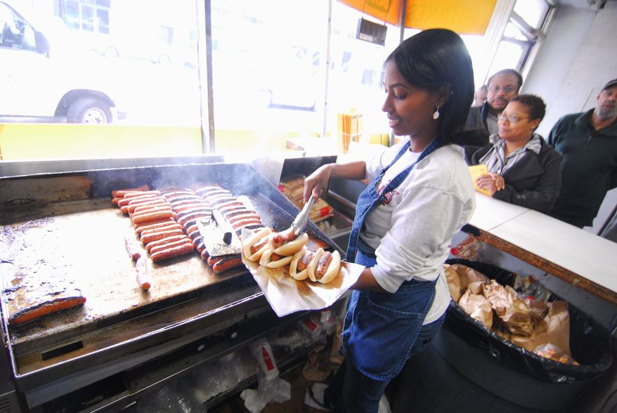 The kitchen at Ben's Chili Bowl churns out its take on the iconic capital food known as a half-smoke, often smothered in chili. (The Washington Times)