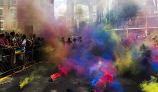 Members of the Black Lives Matter movement stand amidst colored clouds from smoke grenades at the annual Pride Parade in Toronto on Sunday, July 3, 2016. (Mark Blinch/The Canadian Press via AP)