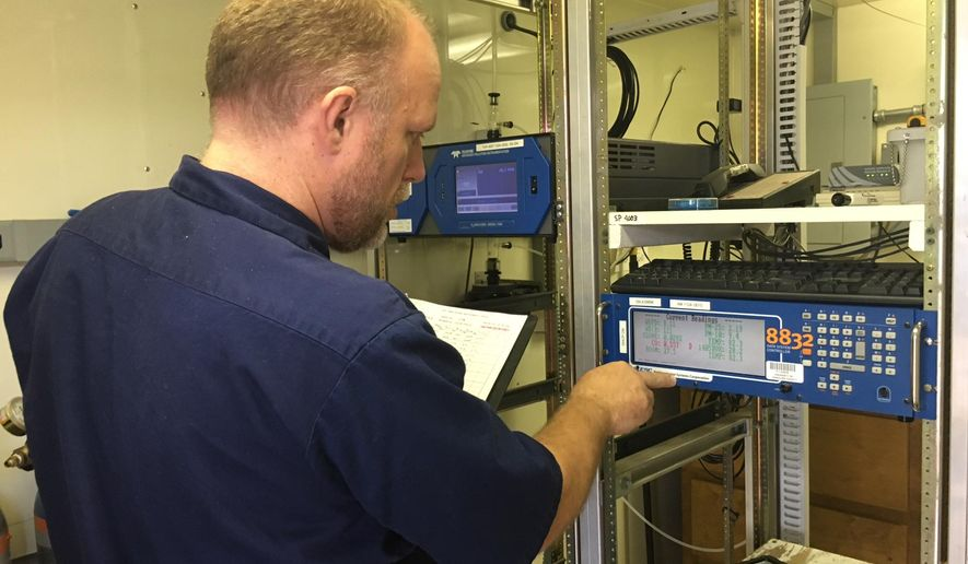 Ben Davis, an air monitoring manager at the Maricopa County Air Quality Department in Phoenix, looks at an ozone monitor and data monitor on Friday, July 1, 2016. The Phoenix metro area is seeing a sharp rise this year in the number of days it has exceeded the federal health standard for the acceptable level of ozone in the air. (Bob Huhn /Maricopa County Air Quality Department via The AP)