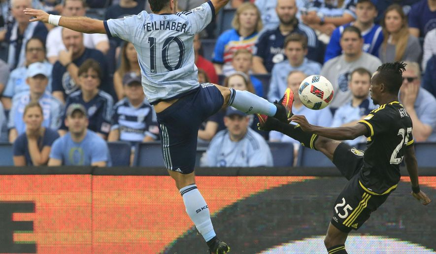 Sporting Kansas City midfielder Benny Feilhaber (10) challenges Columbus Crew defender Harrison Afful (25) during the first half of an MLS soccer match in Kansas City, Kan., Sunday, July 3, 2016. (AP Photo/Orlin Wagner)