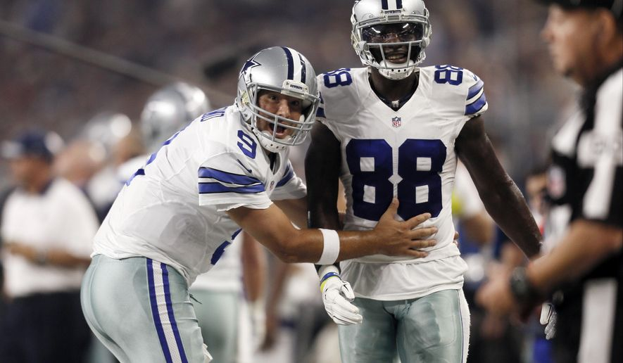 FILE - In this Sept. 13, 2015, file photo, Dallas Cowboys quarterback Tony Romo (9) and wide receiver Dez Bryant (88) react during the first half of an NFL football game against the New York Giants in Arlington, Texas. Both are anxious to get on the field together after injuries kept them apart most of last season, when Dallas slid from first to worst in the NFC East. (AP Photo/Brandon Wade, File)