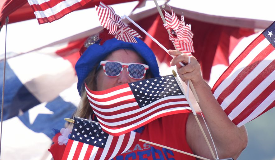 "A woman is surrounded by American flags as she rides a boat at the Lake Cherokee Annual Boat Parade in Longview, Texas Saturday,  July 2, 2016. Participants in the event chose to decorate their boats in their a patriotic theme or open theme. Themed boats included the Olympics, super heroes, ""Duck Dynasty"" and Donald Trump.   (Sarah A. Miller/Tyler Morning Telegraph via AP)"
