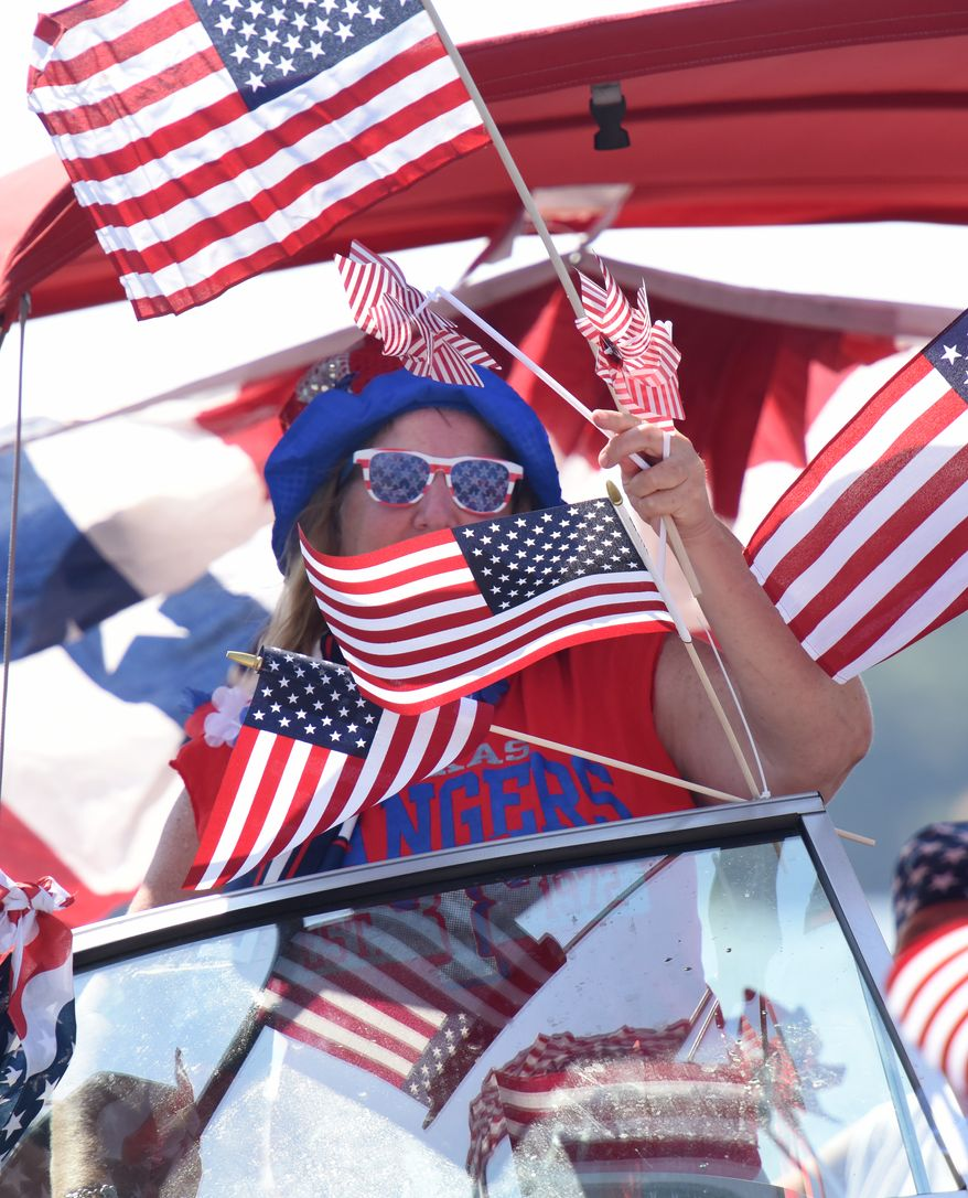 """A woman is surrounded by American flags as she rides a boat at the Lake Cherokee Annual Boat Parade in Longview, Texas Saturday,  July 2, 2016. Participants in the event chose to decorate their boats in their a patriotic theme or open theme. Themed boats included the Olympics, super heroes, """"Duck Dynasty"""" and Donald Trump.   (Sarah A. Miller/Tyler Morning Telegraph via AP)"""