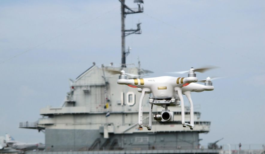 In this photo taken Wednesday, June 29, 2016, a drone, similar to those that will be taking up-close pictures of Fourth of July fireworks at the Patriots Point Naval and Maritime Museum in Mount Pleasant, S.C., is flown near the aircraft carrier USS Yorktown at the museum. The up-close video will be projected on the sides of the aircraft carrier during the Independence Day celebration. (AP Photo/Bruce Smith)