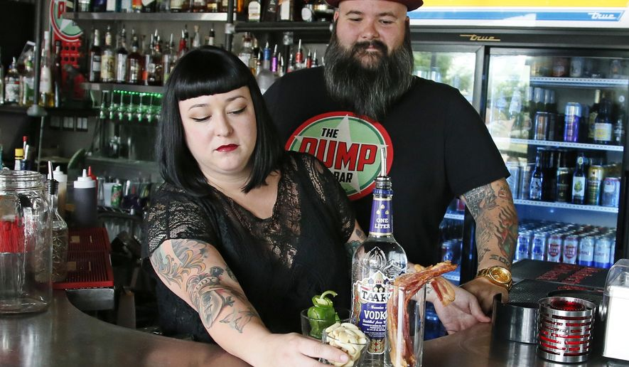 In this July 1, 2016 photo, Pump Bar owners Hailey McDermid, left, and Ian McDermid, right, are pictured with some of the ingredients that they had used to make infused alcohol at the Pump Bar in Oklahoma City. Pump's weeknight manager Colin Grizzle was arrested in April after Oklahoma City police issued the bar a second citation for improperly storing infused liquor. (AP Photo/Sue Ogrocki)