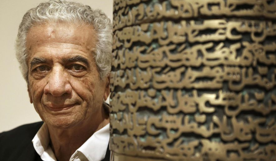 """FILE - In this Feb. 9, 2015 file photo, Iranian artist Parviz Tanavoli stands near a detail of his sculpture """"Poet Turning into Heech,"""" at the Davis Museum on the campus of Wellesley College in Wellesley, Mass. Tanavoli says he has been barred from leaving the country while trying to travel to London. (AP Photo/Steven Senne, File)"""