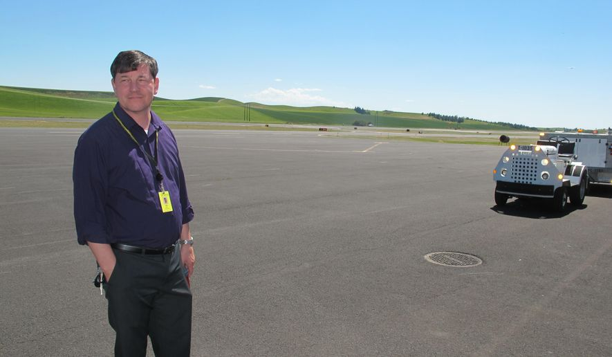 Pullman-Moscow Regional Airport manager Tony Bean stands on the tarmac at the airport in Pullman, Wash., Tuesday, June 28, 2016.  Plans to expand the runway at the Pullman-Moscow Regional Airport have run into a snag, as the proposal could lead to the demolition of dozens of buildings at Washington State University.  The airport needs to lengthen and widen its main runway under Federal Aviation Administration rules because it is being served by larger planes, Bean said.  (AP Photo/Nicholas K. Geranios)