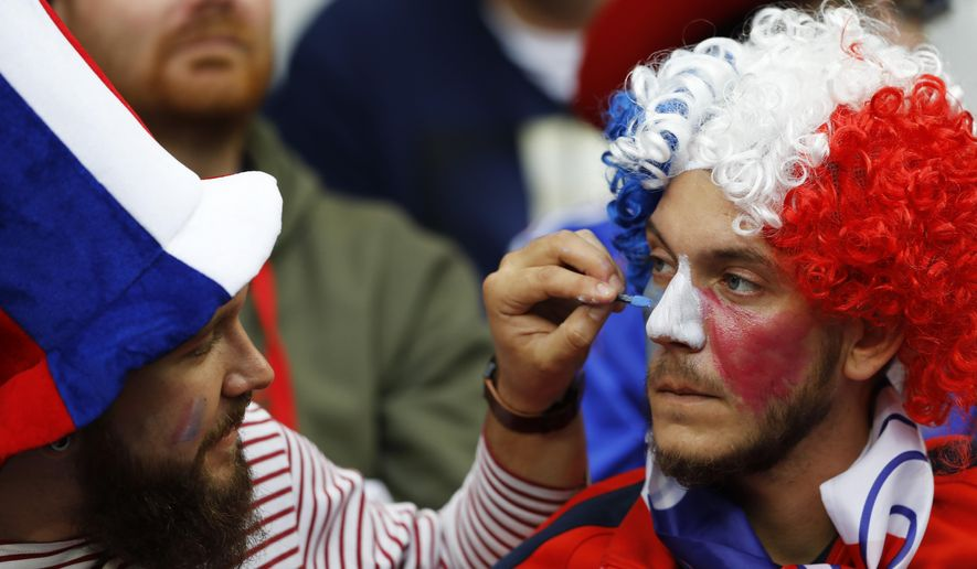 A France supporter is painted with the French colors prior to the Euro 2016 quarterfinal soccer match between France and Iceland, at the Stade de France in Saint-Denis, north of Paris, France, Sunday, July 3, 2016. (AP Photo/Frank Augstein)