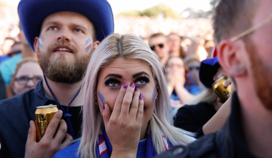 Iceland soccer fans watch France score during the Euro 2016 quarterfinal match between Iceland and France on a large screen in Reykjavik, Iceland, Sunday July 3, 2016. (AP Photo/Brynjar Gunnarsson)