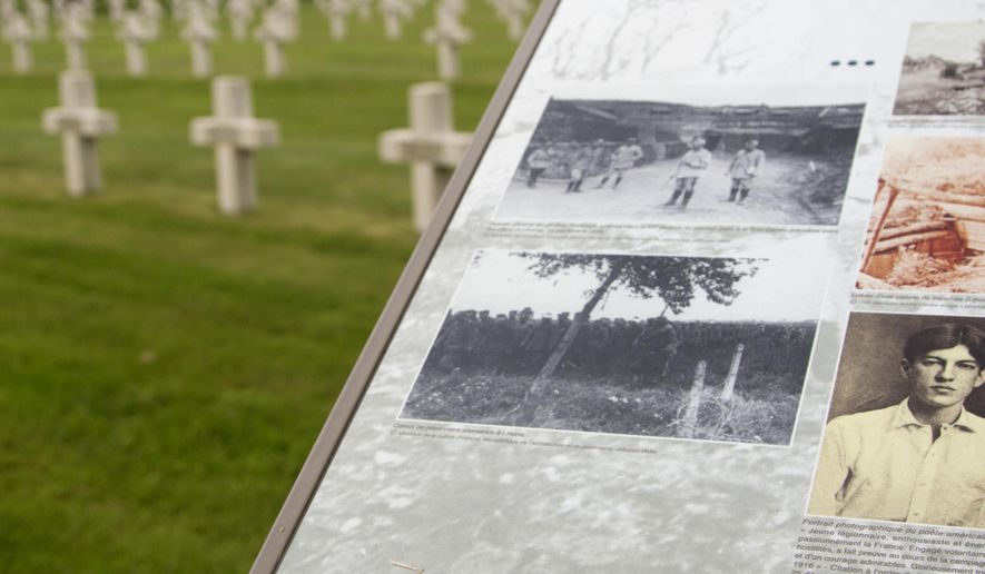 In this photo taken on Wednesday, June 8, 2016, an information board with a photograph of Alan Seeger guides visitors through the French National Necropolis of Lihons, in Lihons, France. American poet Alan Seeger died a century ago on July 4th during the 1916 Battle of the Somme in northern France, already fighting for a global, common cause that bound dozens of countries together at a time when the United States was still a bystander, reluctant to get involved in a faraway war. (AP Photo/Virginia Mayo)
