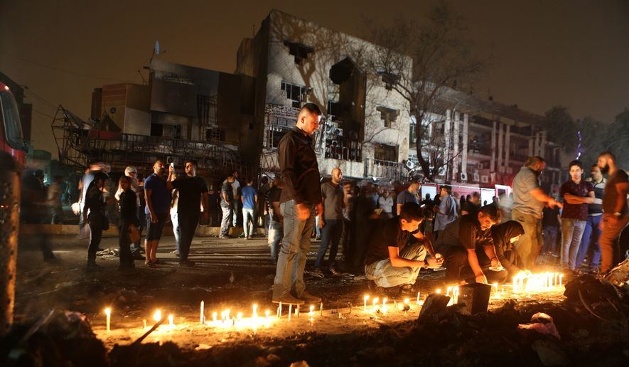 People light candles at the scene of a massive car bomb attack in Karada, a busy shopping district where people were shopping for the upcoming Eid al-Fitr holiday, in the center of Baghdad, Iraq, Sunday, July 3, 2016. More than 100 people died Sunday in a car bombing that Islamic State said it carried out, an official of the Iraqi Interior Ministry said. (AP Photo/Hadi Mizban)