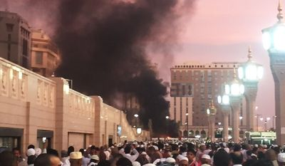 In this photo provided by Noor Punasiya, people stand by an explosion site in Medina, Saudi Arabia, Monday, July 4, 2016. State-linked Saudi news websites reported an explosion Monday near one of Islam's holiest sites in the city of Medina, as two suicide bombers struck in different cities. (Courtesy of Noor Punasiya via AP)